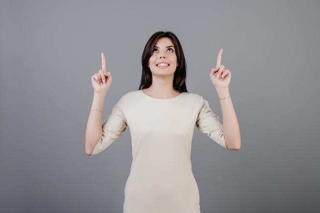 Schöne brunettefrau, die die finger oben lokalisiert über grau lächelt und zeigt