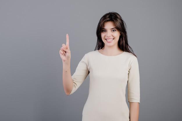 Schöne brunettefrau, die einen finger getrennt über grau zeigt