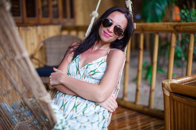 Schöne brunettefrau, die in der hängematte im exotischen hotel auf philippinen sich entspannt