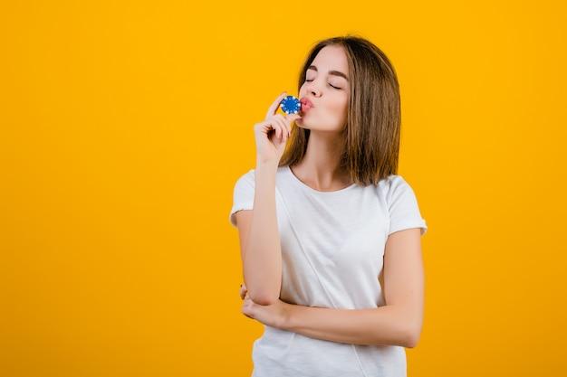 Schöne brunettefrau, die schürhakenchip vom on-line-kasino für das glück getrennt über gelb küsst