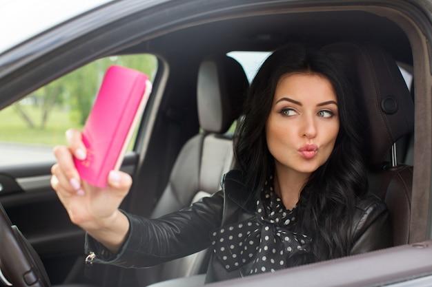 Schöne brunettefrau, die selfie im auto tut