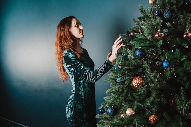 Schöne brunettefrau, die weihnachtsbaum verziert