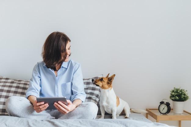 Schöne brunettefrau in den pyjamas sitzt auf bett im schlafzimmer mit ihrem jack- russellterrierhund.