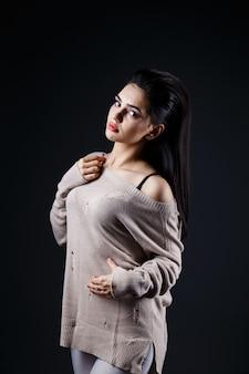 Schöne brunettefrau in der beige strickjacke
