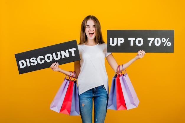 Schöne brunettefrau mit bunten einkaufstaschen und copyspace simsen die 70% zeichenfahne, die über gelb lokalisiert wird