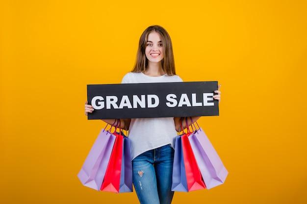 Schöne brunettefrau mit bunten einkaufstaschen und copyspace simsen die großartige verkaufszeichenfahne, die über gelb lokalisiert wird
