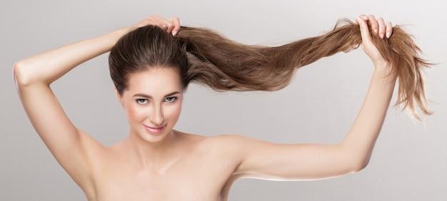 Schöne brunettefrau mit dem geraden langen haar. pflege der haare