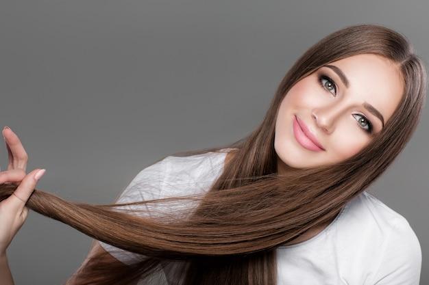 Schöne brunettefrau mit dem glänzenden geraden langen haar. pflege der haare
