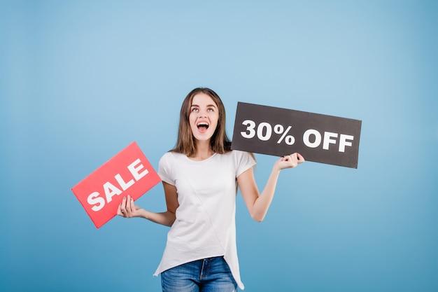 Schöne brunettefrau mit der copyspace text 30% verkaufszeichenfahne getrennt über blau
