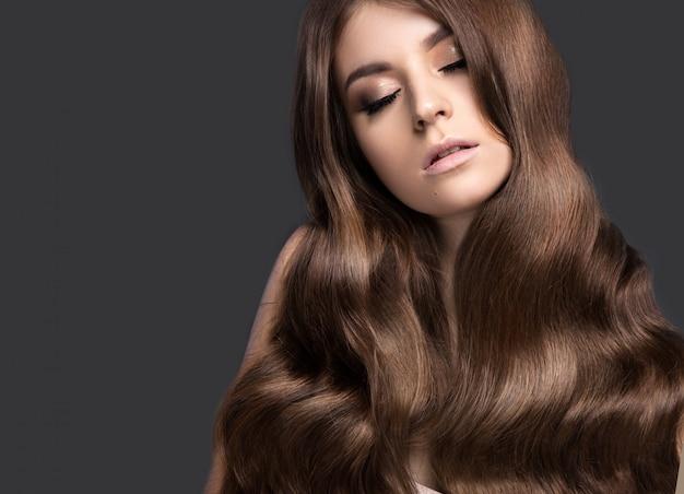 Schöne brunettefrau mit einem tadellos lockenhaar und einem klassischen make-up