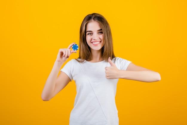 Schöne brunettefrau mit schürhakenchip vom on-line-kasino, welches die daumen oben getrennt über gelb zeigt