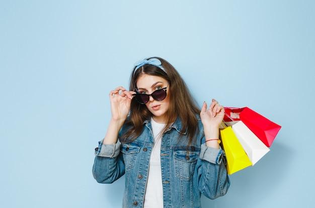 Schöne brunettefrau mit sonnenbrille genießt das einkaufen, das sie auf einem blauen hintergrund gemacht hat