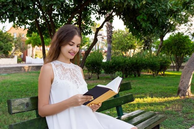 Schöne brunettefrau sitzt auf der bank und liest ein interessantes buch auf stadtstraße