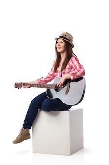 Schöne brunettefrau sitzt auf ihrem bein und spielt gitarre. getrennt über weißem hintergrund.