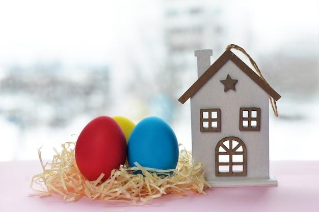 Schöne bunte eier auf einem hellen hintergrund mit einem holzhaus