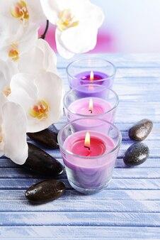 Schöne bunte kerzen, spa-steine und orchideenblume, auf farbigem holztisch, auf hellem hintergrund