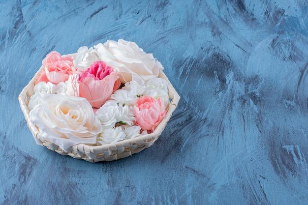 Schöne bunte rosenblume im weidenkorb auf blau.