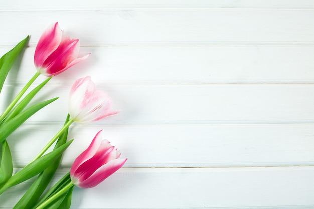 Schöne bunte tulpen auf weißem holzschreibtisch.