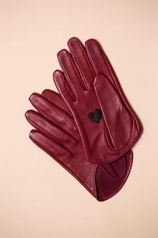 Schöne burgunderfarbene lederhandschuhe mit einem herzen auf der handfläche