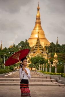 Schöne burmesische mädchen in trachten tragen sie tanaka-pulver auf die wangen und den blick auf die shwedagon-pagode, myanmar