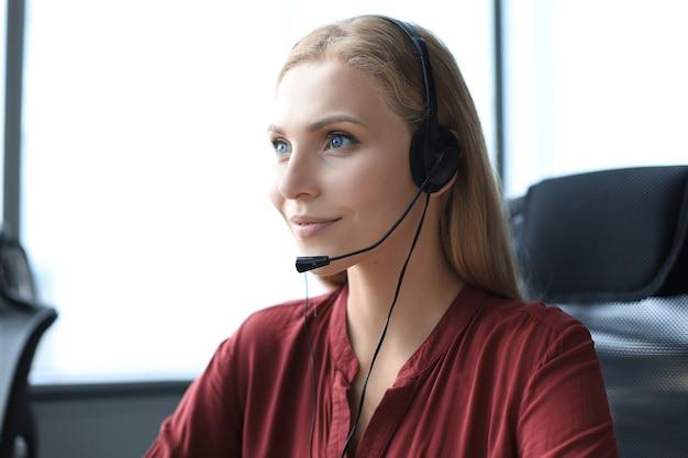 Schöne call-center-mitarbeiterin mit kopfhörern arbeitet im modernen büro.