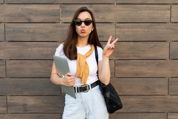 Schöne charmante junge brunet-frau, die die kamera mit computer-laptop und sonnenbrille anschaut, die friedensgeste mit küssenden lippen in weißem t-shirt und hellblauer jeans auf der straße zeigt.