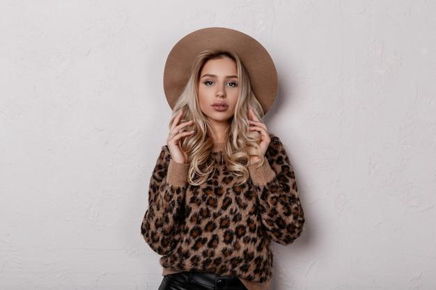 Schöne charmante junge frau in einem trendigen stilvollen leopardenpullover in trendigen schwarzen lederhosen und einem beigen hut, der drinnen aufwirft