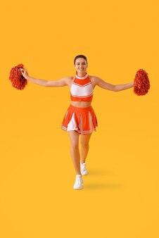 Schöne cheerleaderin auf farboberfläche