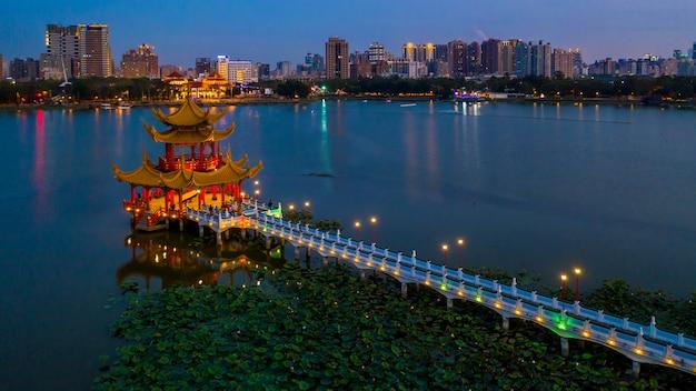 Schöne chinesische pagode mit kaohsiung-stadt im hintergrund nachts, wuliting, kaohsiung, taiwan.