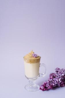 Schöne dalalgona trinken einen schaumigen kaffee in einer transparenten tasse und blüht lila bis lila il lila wand. neben dem becher befindet sich ein marshmallow und ein zweig flieder.