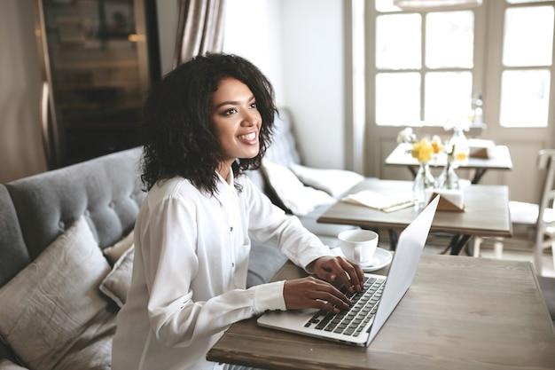 Schöne dame, die am laptop im restaurant arbeitet. hübsches afroamerikanisches mädchen, das am computer im café tippt