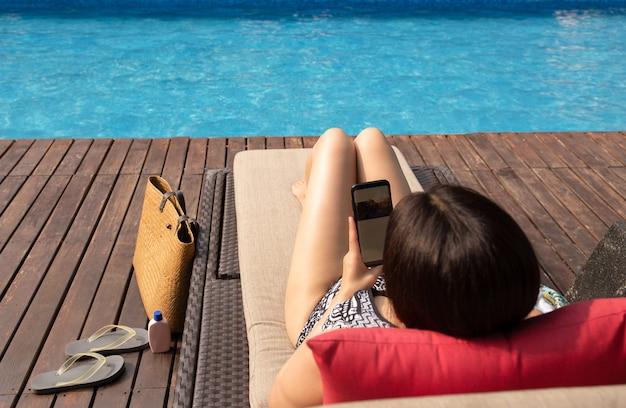Schöne dame, die den handy liegt auf stuhl durch swimmingpool mit strandtasche verwendet.