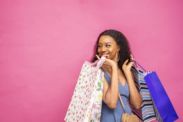 Schöne dame, die einkaufstüten trägt und lächelt