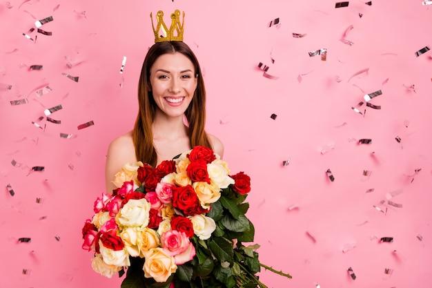 Schöne dame, die gegen die rosa wand mit einem strauß bunter rosen aufwirft