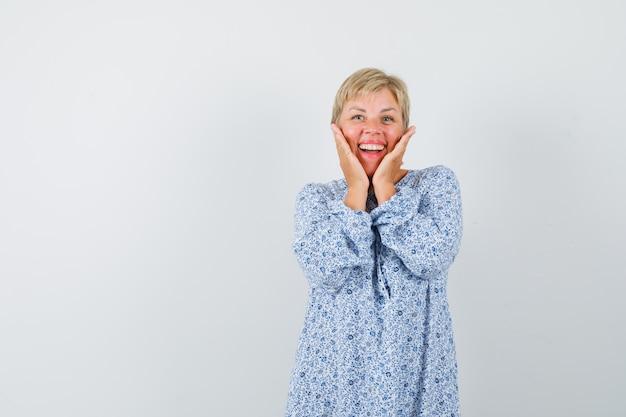 Schöne dame, die hände auf ihren wangen in gemusterter bluse hält und erfreut aussieht. vorderansicht. freier speicherplatz für ihren text