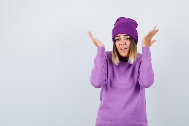 Schöne dame, die hilflose geste in pullover, mütze zeigt und hilflos aussieht. vorderansicht.