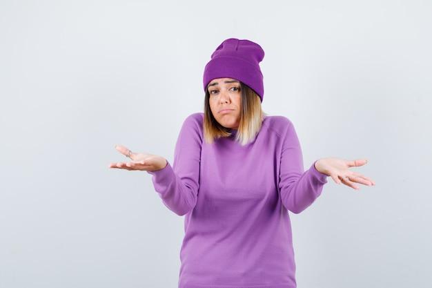Schöne dame, die hilflose geste in pullover, mütze zeigt und unentschlossen aussieht. vorderansicht.