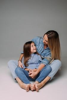 Schöne dame, die ihre tochter auf dem boden umarmt, während sie mit ihr im denim-familienlook posiert.