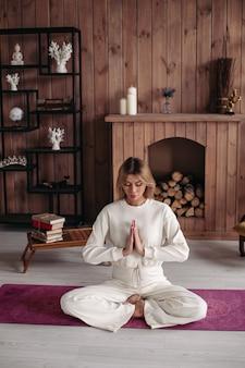 Schöne dame, die im lotussitz trainiert und sitzt, während sie an ihrer wohnung ruht. gesundes und lifestyle-konzept