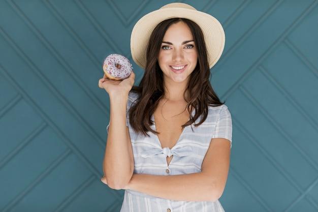 Schöne dame, die in der hand donut hält