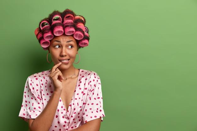 Schöne dame, die maske für gesichtspflege trägt lockenwickler isoliert
