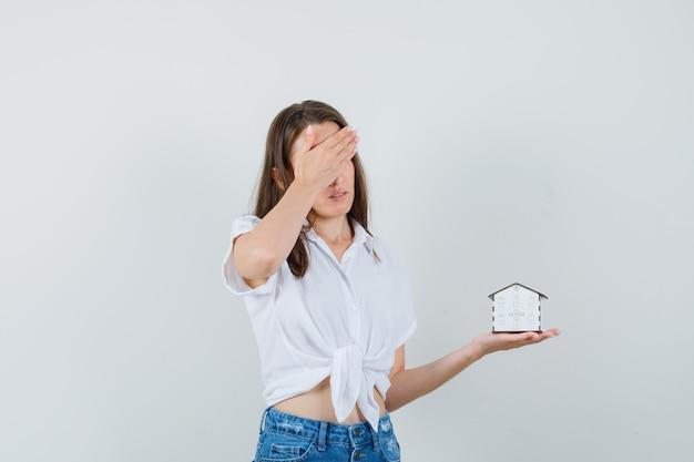Schöne dame, die modellhaus hält, während hand auf ihrem kopf in weißer bluse hält und stressige vorderansicht schaut.