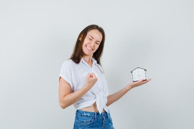 Schöne dame, die modellhaus hält, während siegergeste in der weißen bluse zeigt und glückliche vorderansicht schaut.