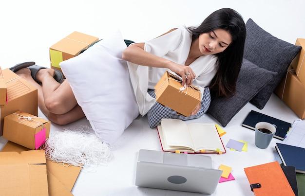 Schöne dame, die sich neben briefkasten legt, laptop und buch verwendet, um daten des online-verkaufs aufzuzeichnen, zum senden zu verpacken, zu hause zu arbeiten, e-commerce