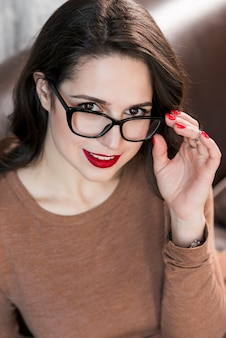 Schöne dame, die über schwarzen brillen kamera betrachtet