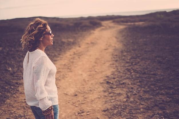 Schöne dame, die vor einem weg an einem trockenen ort der wüste steht. modekleidung und schöne frauen, die spazieren gehen und reisen, um sie zu entdecken. auf ihre seite schauen