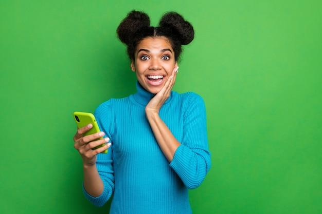 Schöne dame halten telefonhand auf wangenknochen offener mund