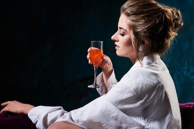 Schöne dame im eleganten abendkleid mit einem glas champagner