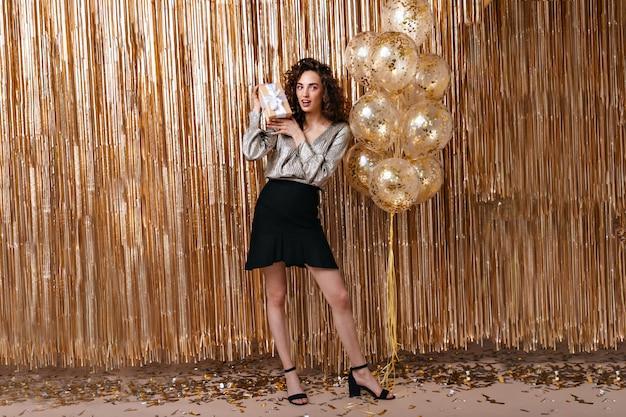 Schöne dame im festlichen outfit, das geschenk auf hintergrund der goldenen luftballons hält