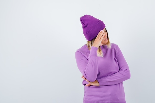 Schöne dame im pullover, mütze, die hand auf dem kopf hält und deprimiert aussieht, vorderansicht.